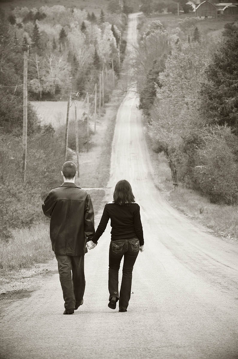 Walking hand in hand down steep country road for country themed Peterborough engagement photography session