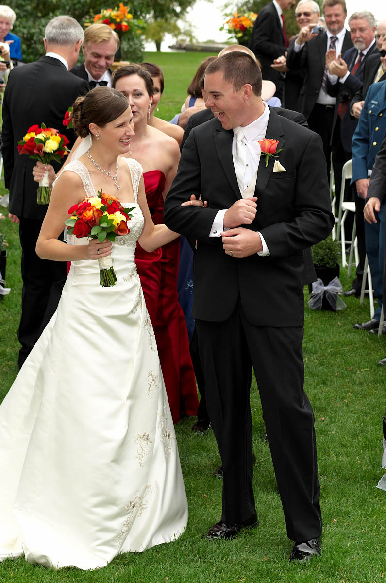 Dynamic groom and bride walk together down ceremony aisle as husband and wife at Eganridge wedding