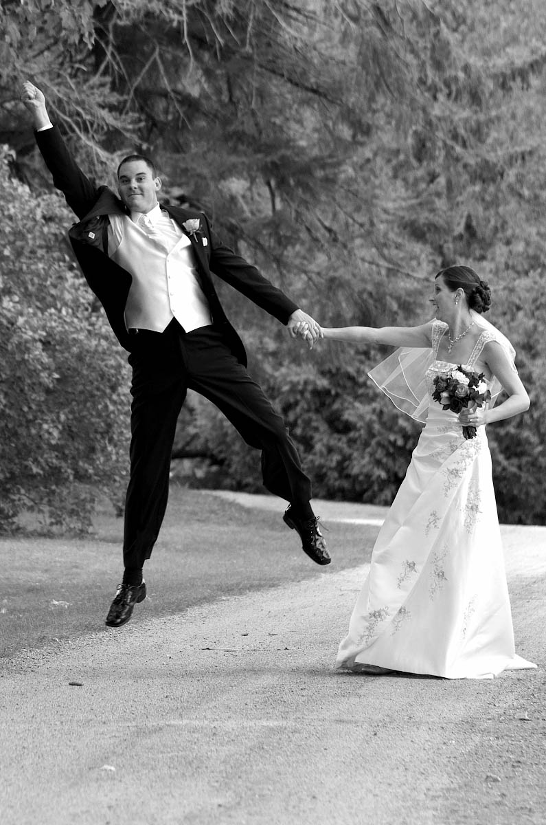 Groom leaps into the air with joy as he strolls with bride down country road at Eganridge Resort wedding in Fenelon Falls