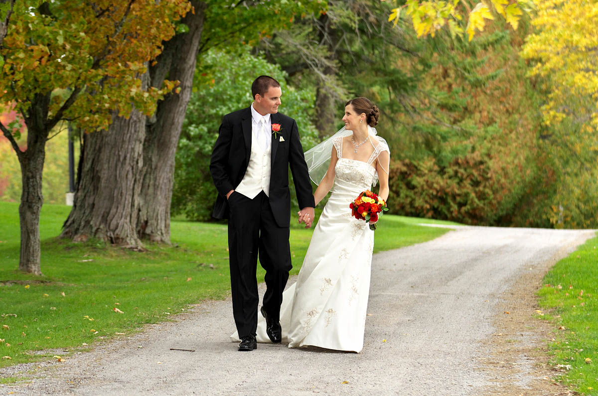 Bride and Groom stroll happily along country road at Eganridge wedding