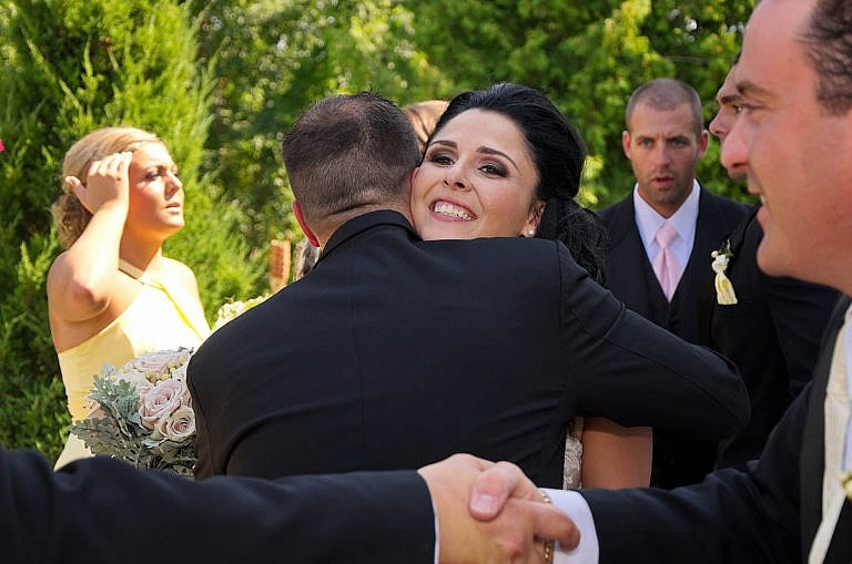 bride hugs groomsman after ceremony