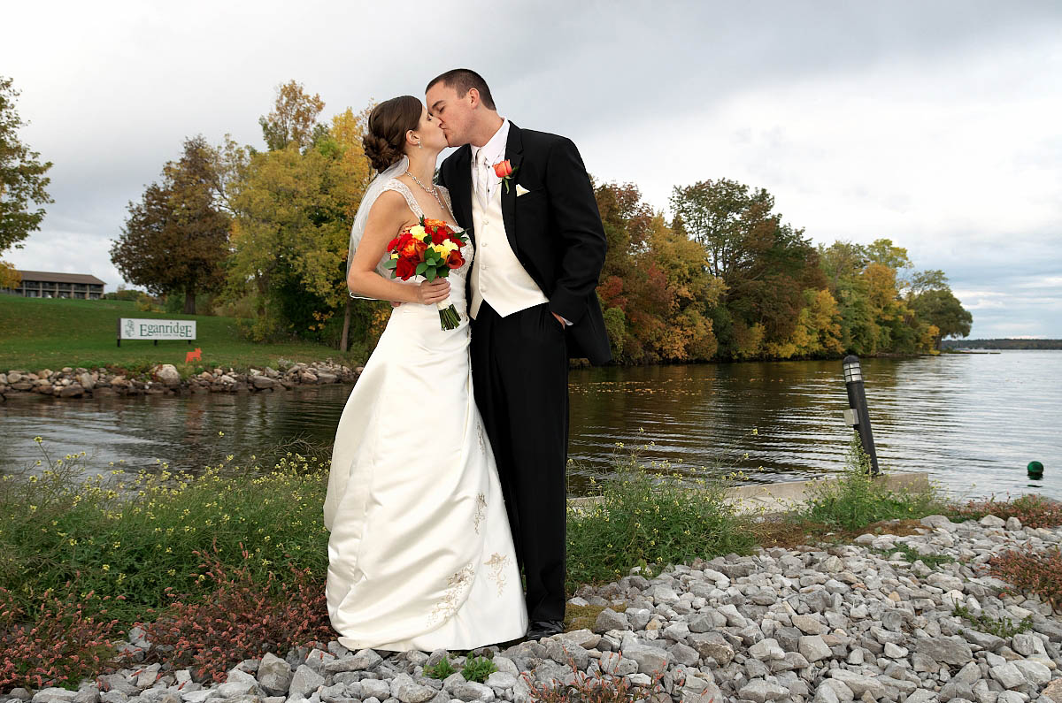 Bride and groom with wildflowers and lake at Eganridge wedding