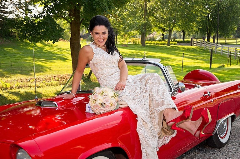bride on hood of cherry red vintage thunderbird