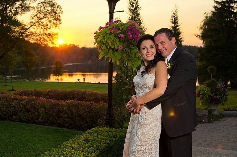 bride and groom embrace at sunset in garden at Royal Ambassador wedding in Caledon