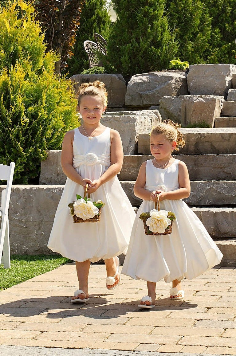 flower girls walk down the aisle together