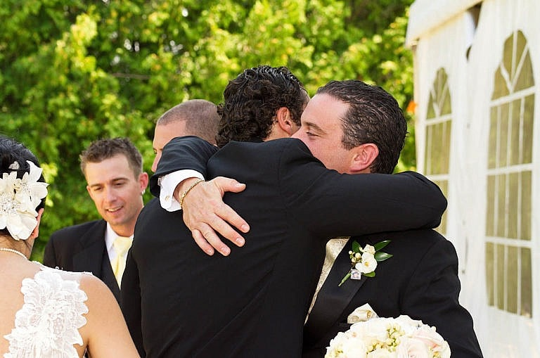 Groom hugs groomsman at Caledon wedding at Royal Ambassador
