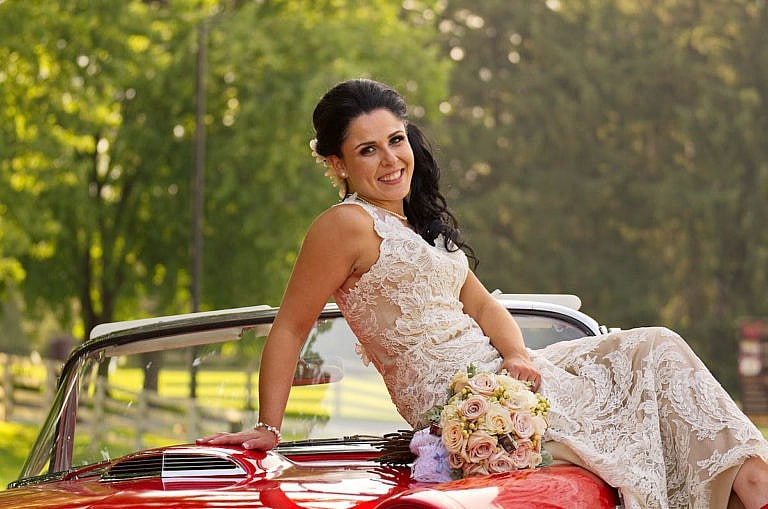 Bride on red vintage car at Caledon wedding at Royal Ambassador