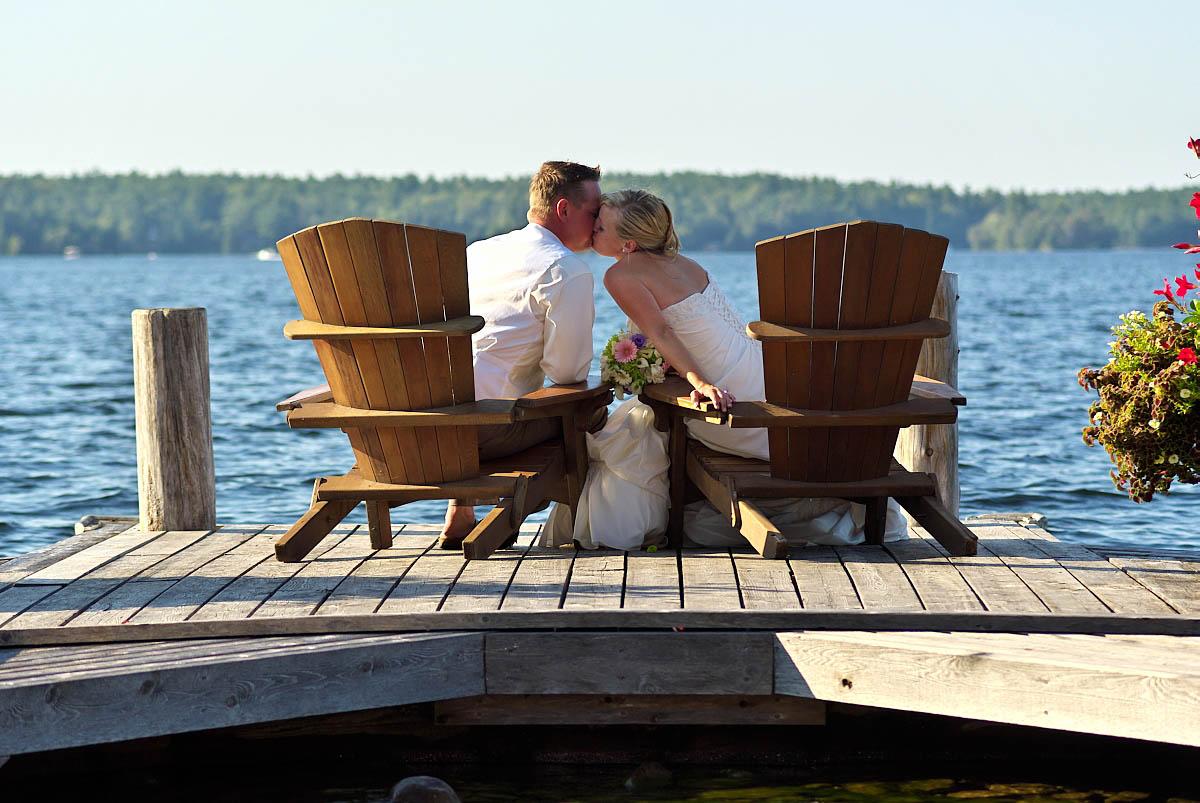 wedding couple kisses in muskoka chairs kissing at stoney lake wedding at irwin inn