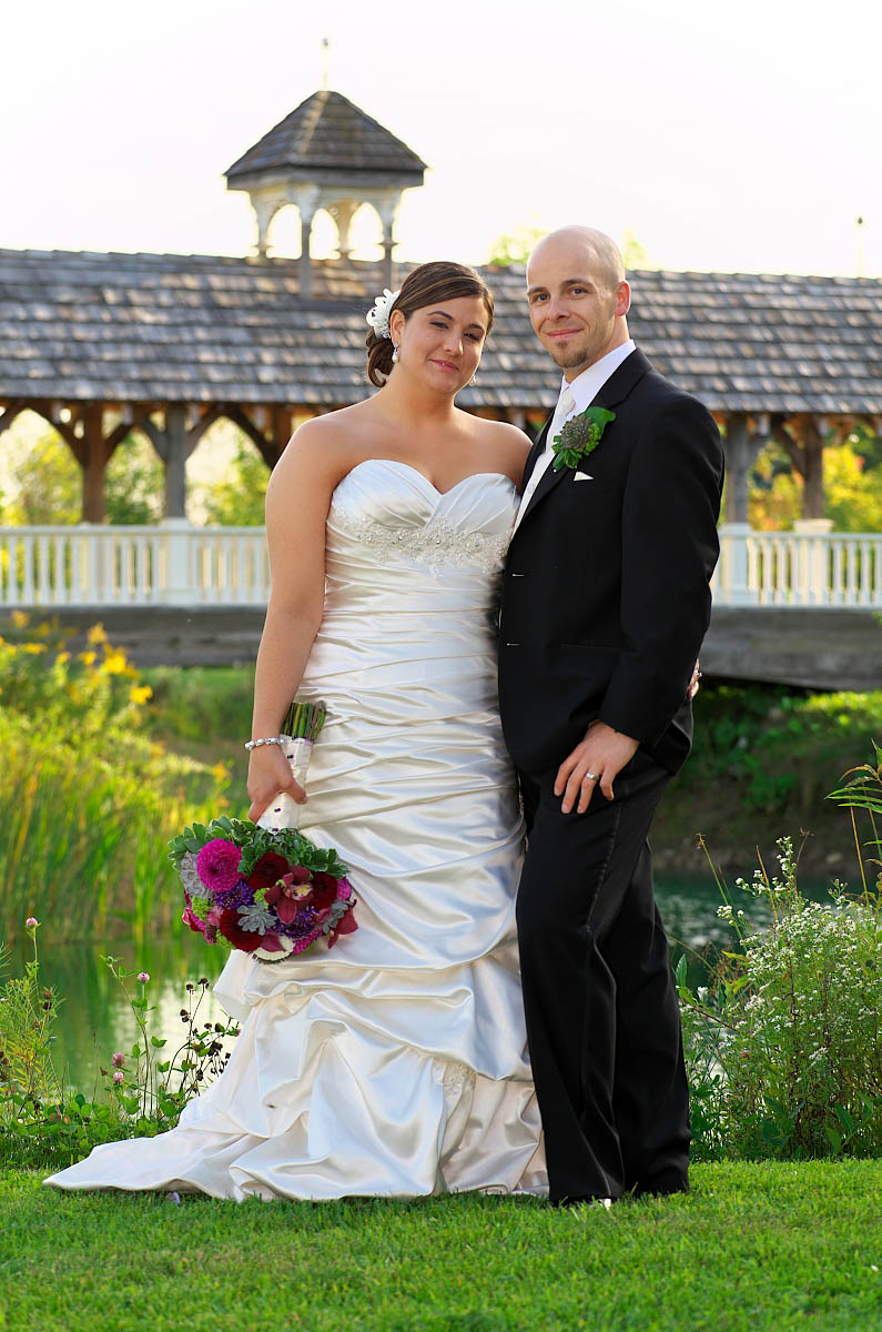 wedding couple in front of covered bridge