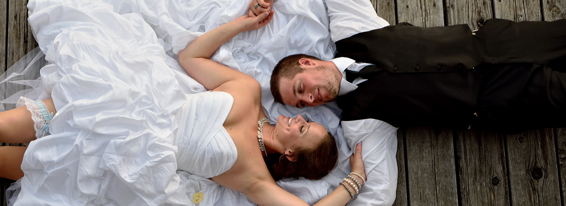 bride and groom lying on dock at discovery harbour in penetanguishene ontario