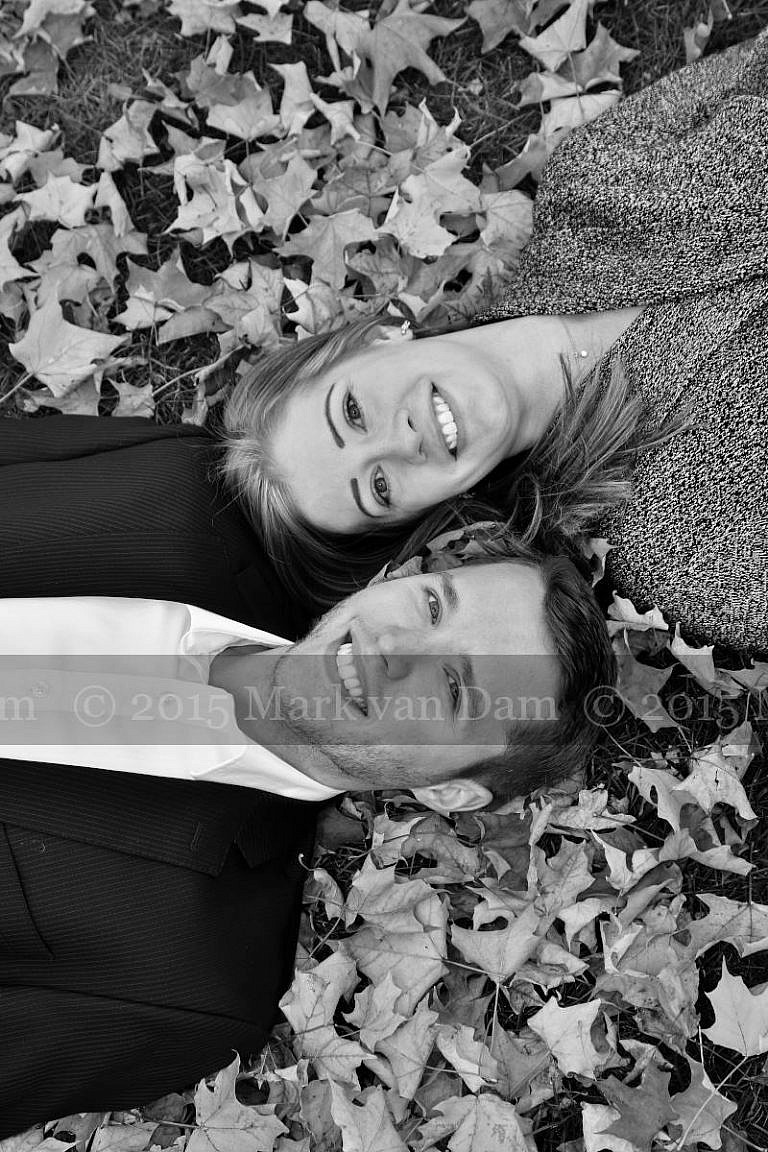 couple lying with heads beside eachother in fall leaves at Orillia photography session