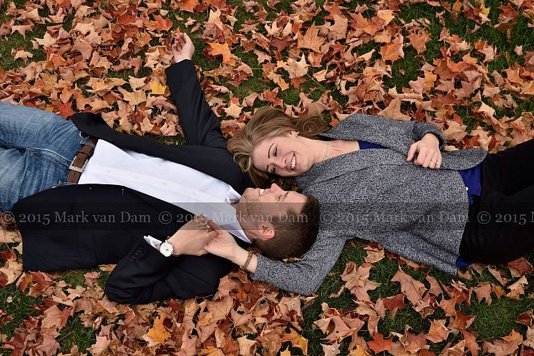 Couple lying head to head in fall leaves