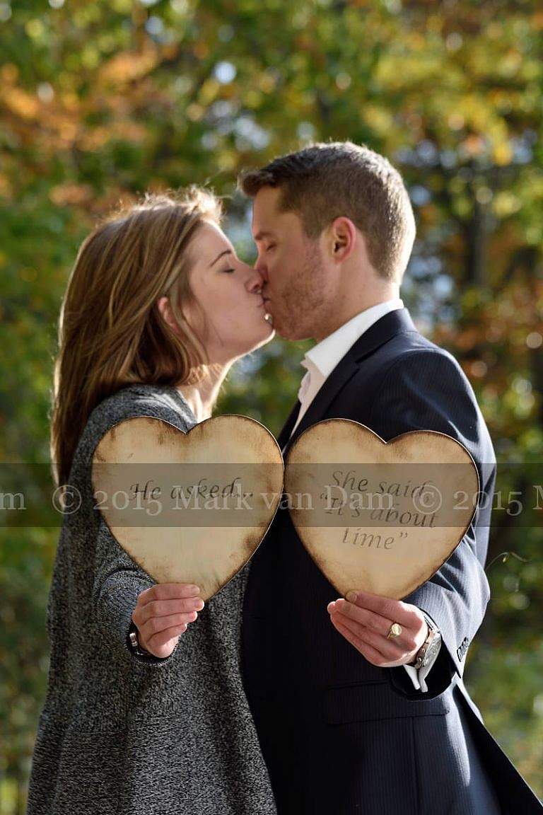 Orillia photographer, couple holds up wedding date sign made from two wooden hearts, save the date