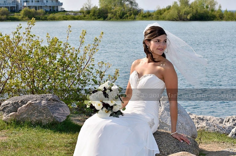Collinwood photographer, Beautiful bride on rocks by water at Cranberry Resort wedding in Collingwood