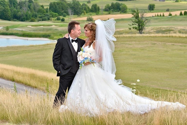 bride and groom overlooking valley at The Club at Bond Head