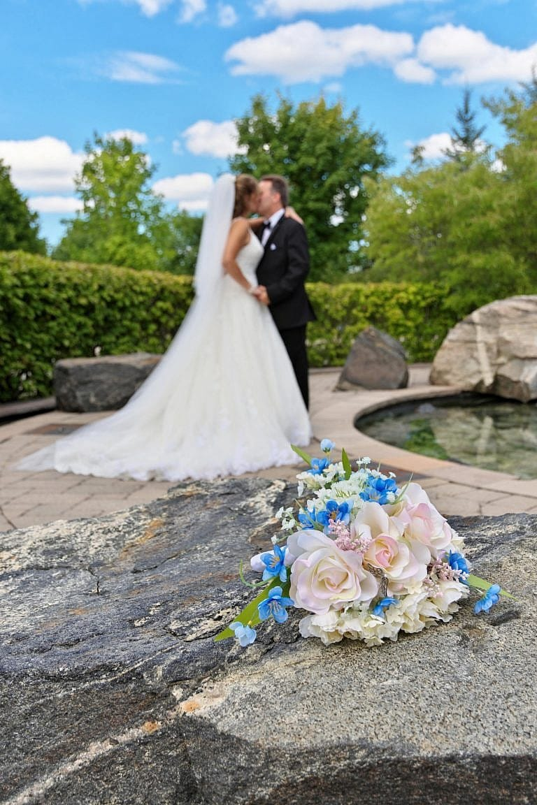 Wedding bouquet with bride and groom in background by fountain at The Club at Bond Head wedding