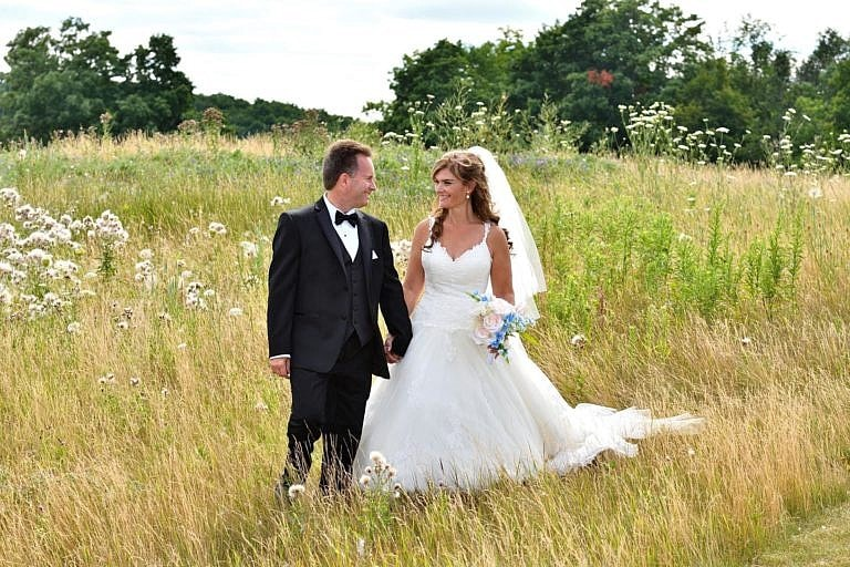 Bride and groom walking through meadow at Bond Head wedding