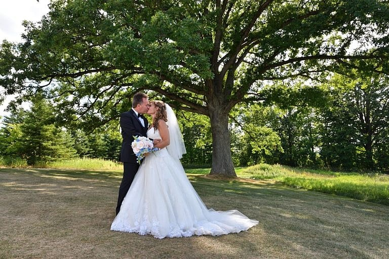 Bride and groom beneath large tree at The Club at Bond Head