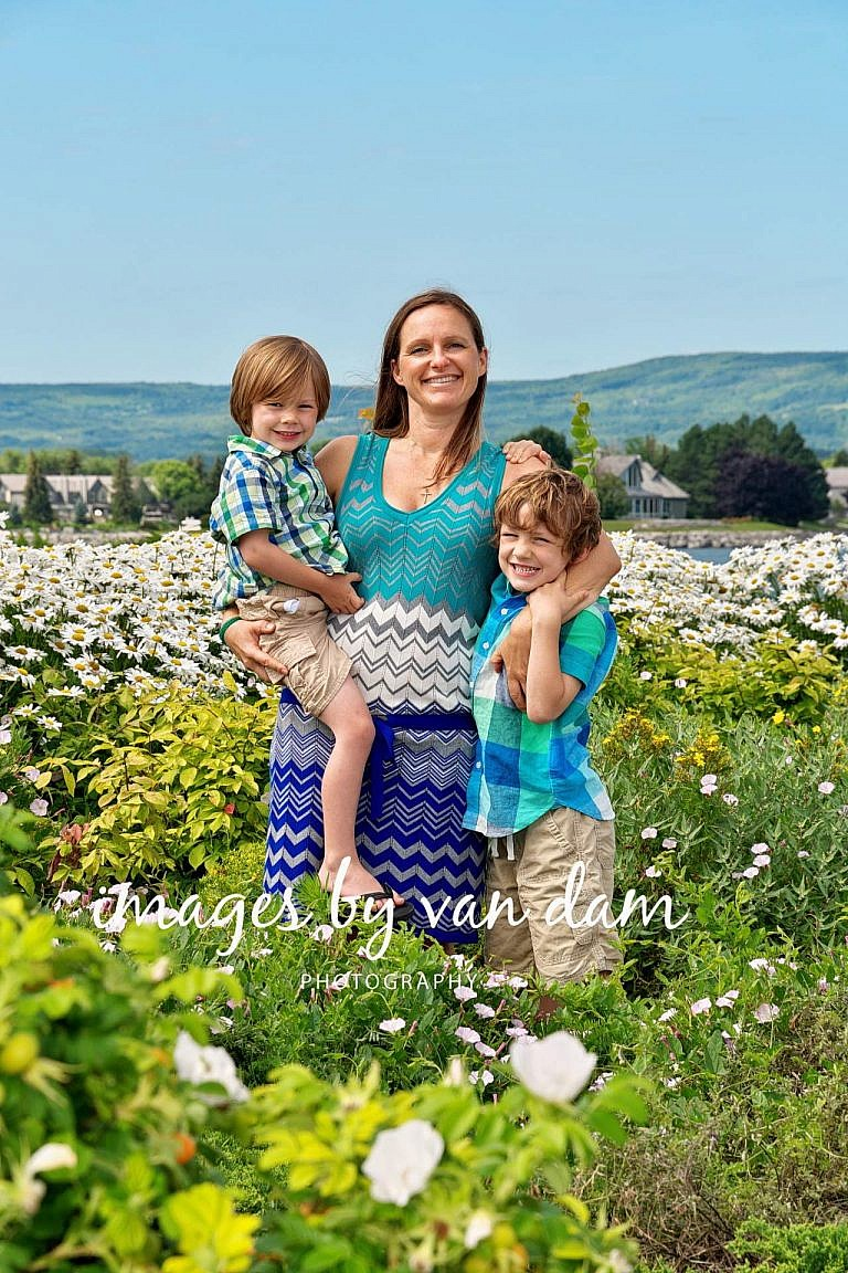 Proud Mom holds her boy close in lush flower garden at the Shipyards collingwood family portraits shipyards portraits collingwood photographer