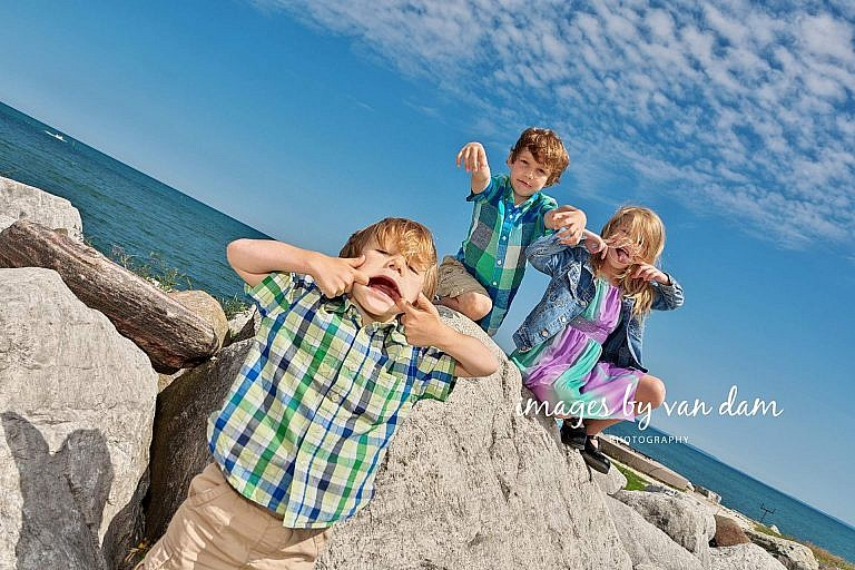 Three Children Make Funny Faces on the rocks by Georgian Bay collingwood family portraits shipyards portraits collingwood photographer
