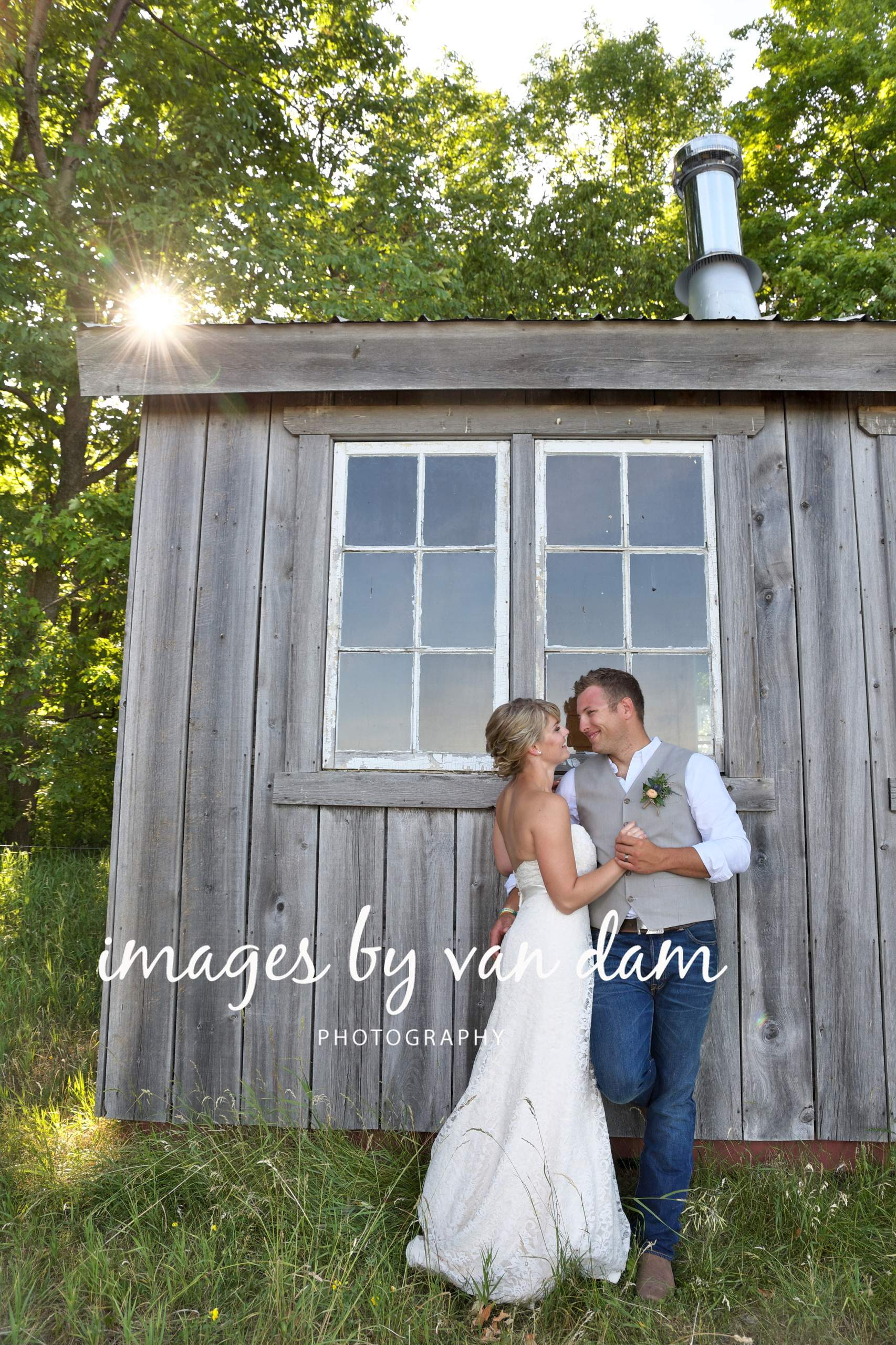 wedding couple embraces by the shed in the back field at a farm wedding in Kawartha Lakes