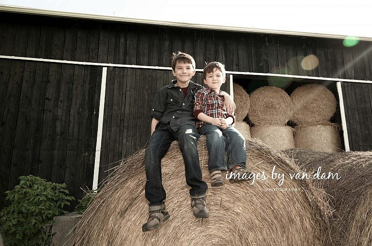 Two young brothers perch on top of a giant hay bale stayner photographer barrie photographer family portraits wasaga photographer collingwood photographer
