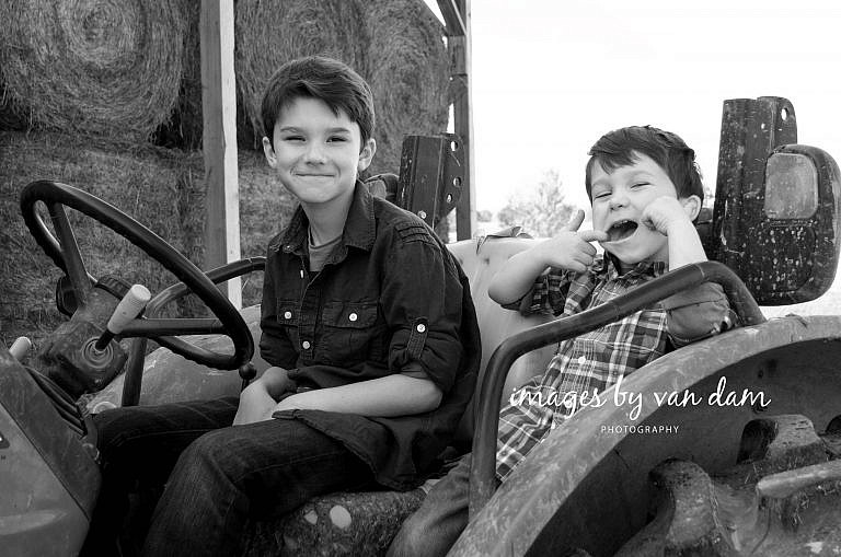 stayner photographer barrie photographer family portraits wasaga photographer collingwood photographerTwo brothers Make Funny Faces while sitting on a John Deere tractor