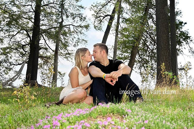 Couple kisses in meadow of flowers at country engagement session in kawartha lakes
