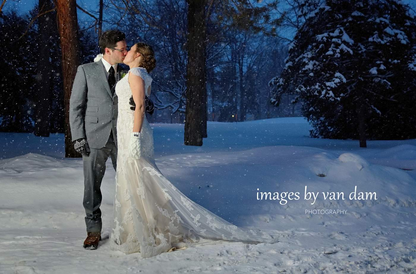 Bride and groom kiss during evening snowfall in at Orillia winter wedding